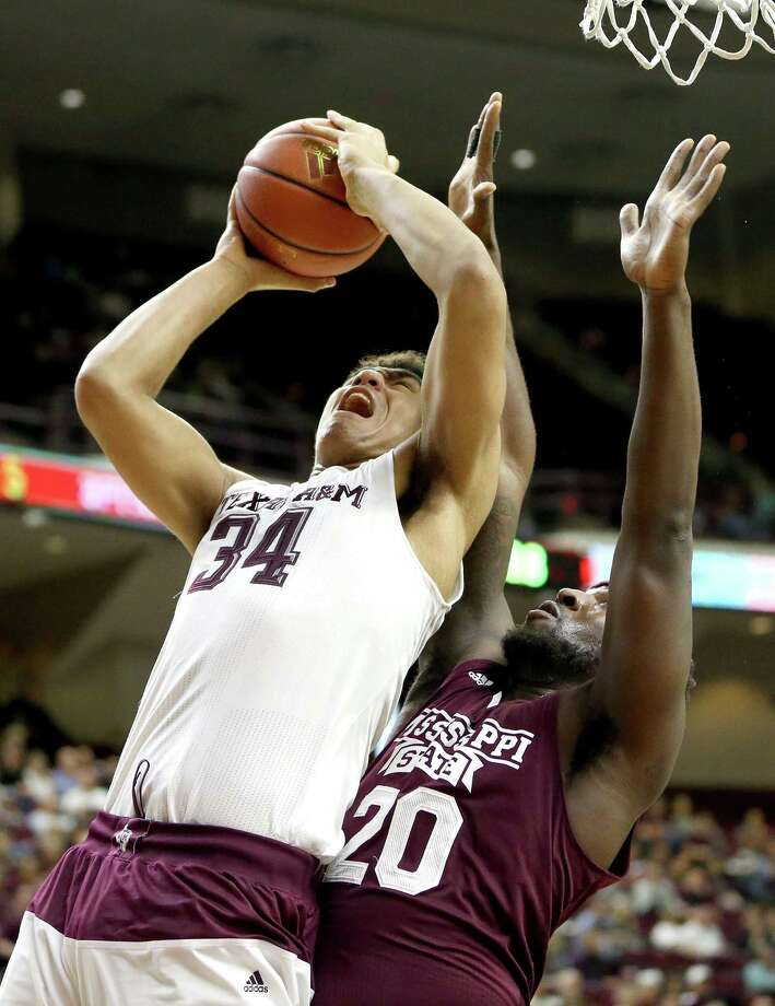 Texas A&M's Tyler Davis, who had 15 points, shoots while being defended by Gavin Ware in the first half. Photo: Sam Craft / Associated Press / FR145148 AP