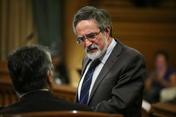 Supervisor Aaron Peskin talks to Supervisor John Avalos  at a Board of Supervisors meeting at City Hall, in San Francisco, California on Tuesday, February 23, 2016.