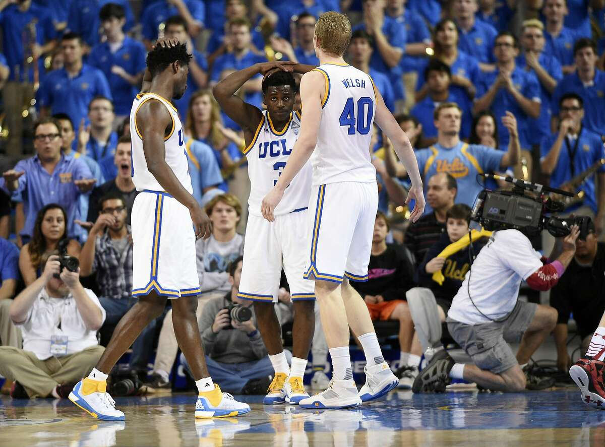 UCLA guard Aaron Holiday, center, guard Isaac Hamilton, left, and center Thomas Welsh, right, gather during the second half of the team's NCAA college basketball game against Utah, Thursday, Feb. 18, 2016, in Los Angeles. Utah won 75-73. (AP Photo/Kelvin Kuo)