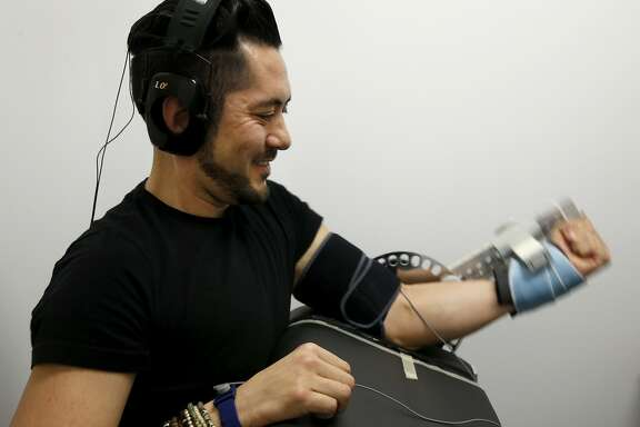 """Tai Klyce performs a series of bicep curls to test the effects of Halo neuropriming headphones in San Francisco, Calif. on Wednesday, Feb. 24, 2016. Halo neuropriming headphones are being tested and used by a number of elite athletes, including Olympic skiers and Major League baseball players, during their regular training sessions. According to the company's website: """"Neuropriming uses pulses of energy to increase the excitability of motor neurons, benefiting athletes in two ways: accelerated strength and skill acquisition""""."""