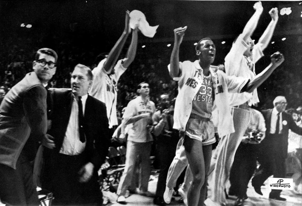 FILE - In this March 19, 1966 file photo, Texas Western College head basketball coach Don Haskins, second from left, and players celebrate after winning the 1966 NCAA basketball championship in College Park, Md. Players from Texas Western's 1966 NCAA championship team gather to open a weekend celebrating the 50th anniversary of the historic victory. With the first all-black starting lineup in a title game, the Miners beat all-white Kentucky in what is considered the most important game in college basketball history. (AP Photo/File)