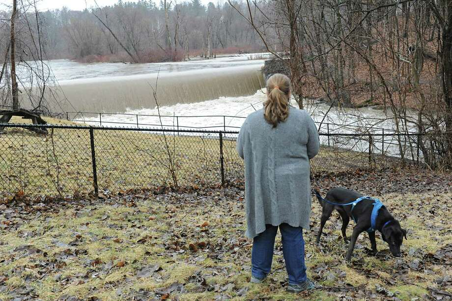 Elizabeth Blaise of Queensbury watches water rush over a dam on the Poesten Kill along Brunswick Rd. as she walks her dog Zoe on Thursday, Feb. 25, 2016 in Troy, N.Y. Blaise works in a building next to the dam. The high creek is causing flooding in bordering yards. (Lori Van Buren / Times Union) Photo: Lori Van Buren / 10035591A