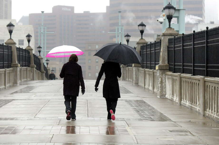 Sherri Gray of Schenectady, left, and Analisa Bastiani-Jesco of Duanesburg protect themselves from the rain as they take their regular lunchtime walk over the pedestrian bridge on Wednesday, Feb. 24, 2016, in Albany, N.Y. (Cindy Schultz / Times Union) Photo: Cindy Schultz, Albany Times Union / Albany Times Union