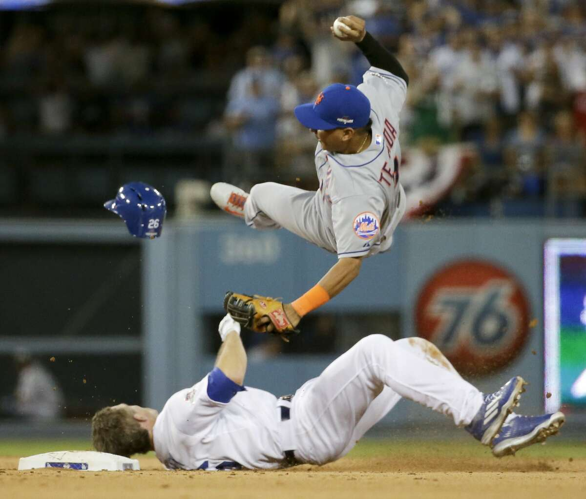 """FILE - In this Oct. 10, 2015, file photo, New York Mets shortstop Ruben Tejada, goes over the top of Los Angeles Dodgers' Chase Utley who broke up a double play during the seventh inning in Game 2 of baseball's National League Division Series, in Los Angeles. Major League Baseball and the players' association have banned rolling block slides to break up potential double plays, hoping to prevent a repeat of the takeout by Dodgers' Chase Utley that broke a leg of Mets Ruben Tejada in last year's playoffs. Under the rules change announced Thursday, Feb. 25, 2016, a runner must make a """"bona fide slide,"""" defined as making contact with the ground ahead of the base, being in position to reach the base with a hand or foot and to remain on it, and sliding within reach of the base without changing his path to initiate contact with a fielder. (AP Photo/Gregory Bull, File)"""