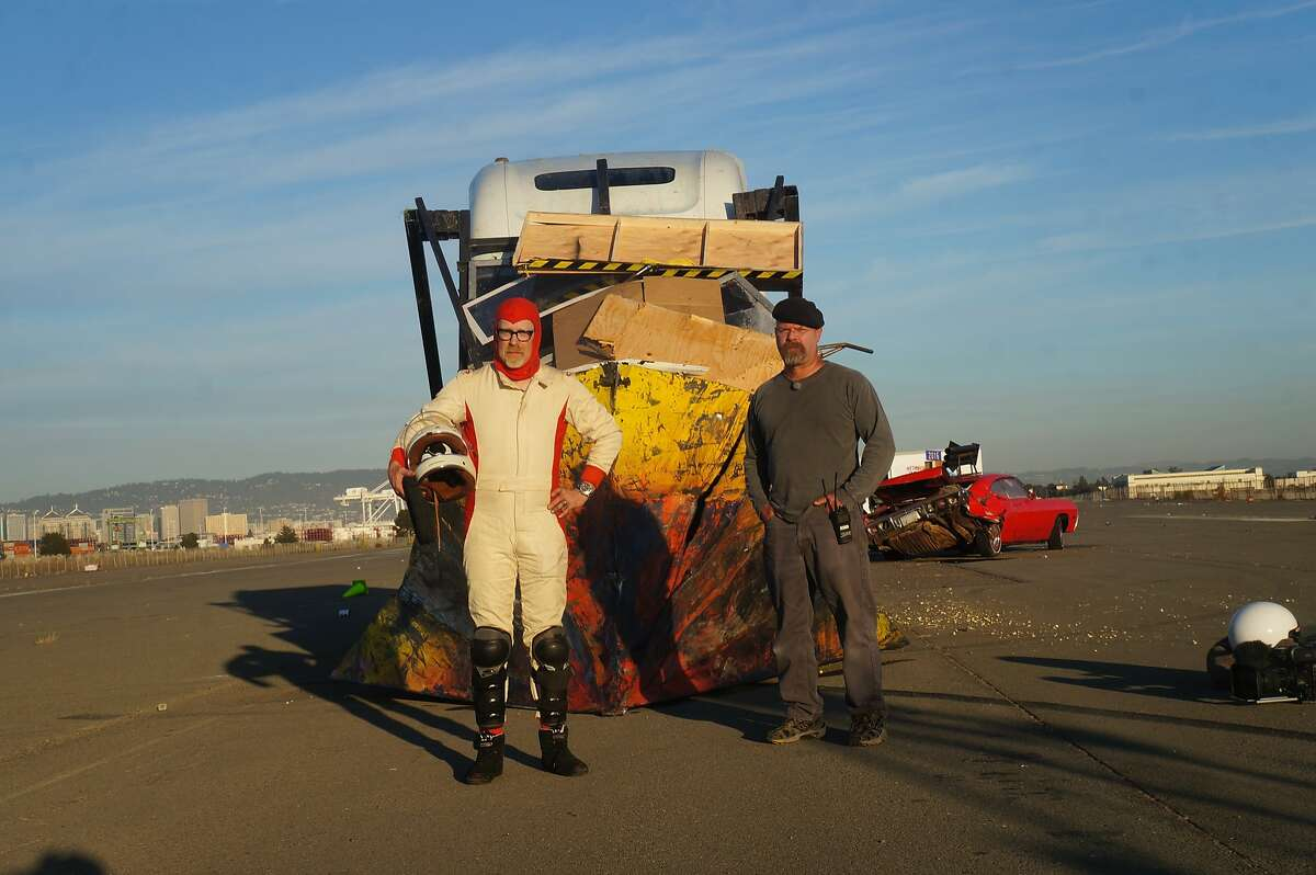 Hosts Adam Savage and Jamie Hyneman stand in front of truck wedge after it has been driven through memorabilia.
