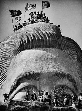 Representatives of tribal groups scale of four-story tall statue of Ferdinand Marcos in La Union Province in a rite to exorcise the former president's spirit from the statue. (Mar. 10, 1986.) Photo by Kim Komenich for the San Francisco Examiner. (Copyright, 2011, Bancroft Library/the University of California)