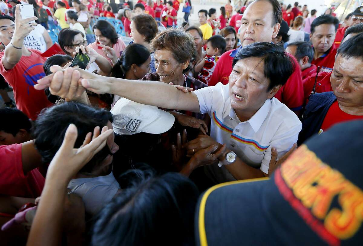 """In this Feb. 22, 2016 photo, Vice-presidential candidate Sen. Ferdinand """"Bongbong"""" Marcos Jr., second right in front, greets supporters during his campaign sortie in Muntinlupa city, southeast of Manila, Philippines. Three decades after a """"people power"""" revolt ousted his dictator father, Sen. Ferdinand Marcos Jr. was wooing voters on the campaign trail this week in his bid to become the Philippines' next vice president."""