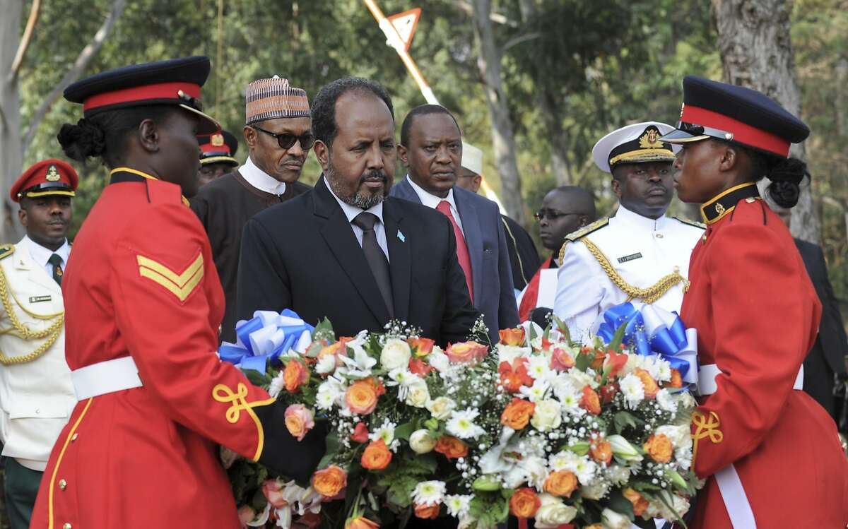 FILE - In this Wednesday, Jan. 27, 2016 file photo, Somalia's President Hassan Sheikh Mohamud, center, lays a wreath as Kenya's President Uhuru Kenyatta, center-right, and President Muhammadu Buhari of Nigeria, center-left, stand behind at an interfaith memorial service honoring Kenyan soldiers killed while on peacekeeping duty in Somalia, at a military barracks in Eldoret, Kenya. Mohamud said Wednesday, Feb. 24, 2016 that at least 180 Kenyan soldiers were killed in Somalia in an extremist attack on their base in January by al-Qaida affiliate al-Shabab.