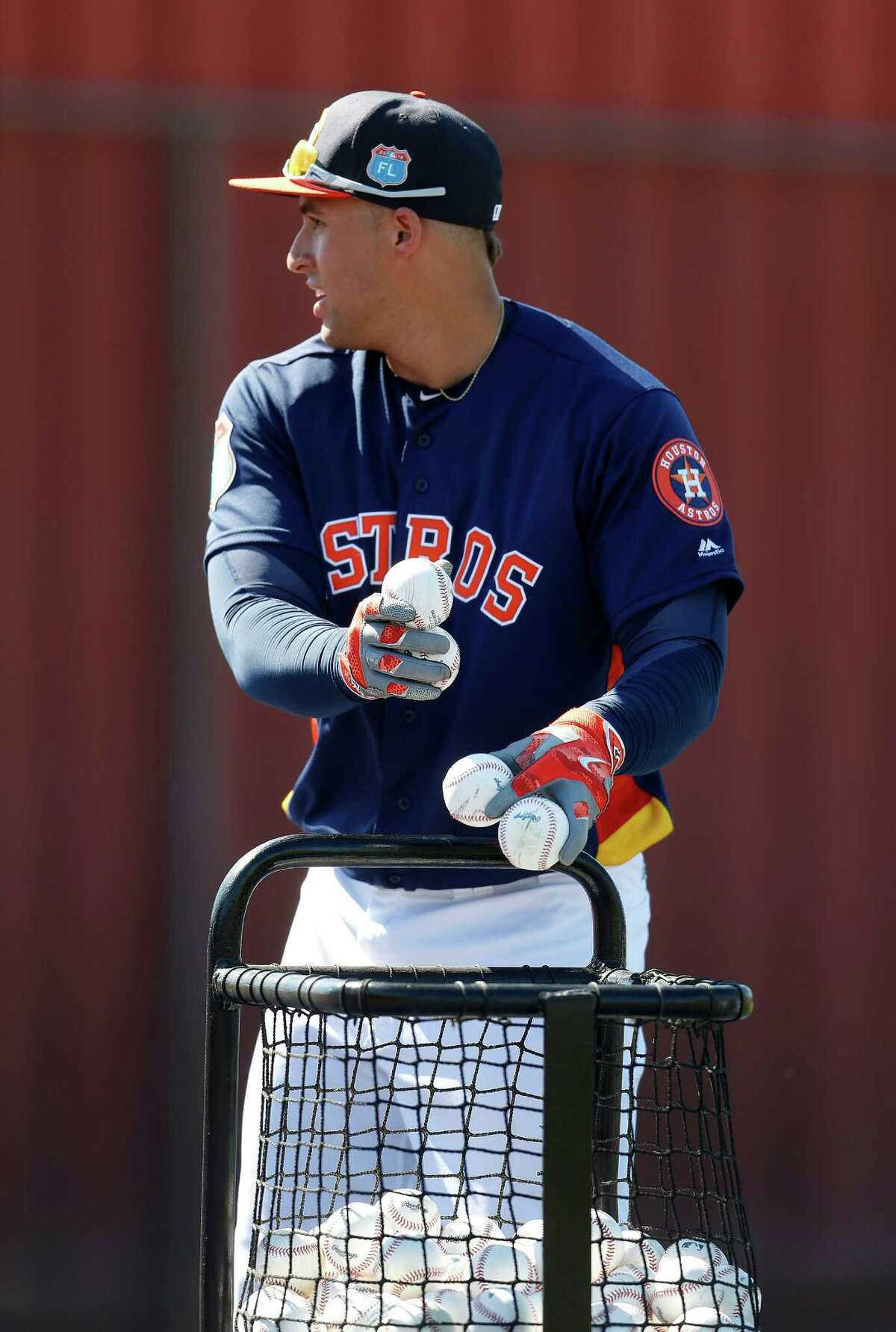 Houston Astros outfielder George Springer picks up balls during batting practice at the Astros spring training in Kissimmee, Florida, Thursday, Feb. 25, 2016.