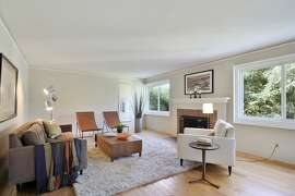 Refreshed hardwood flooring lines a living/dining room that contains one of the home's two fireplaces.