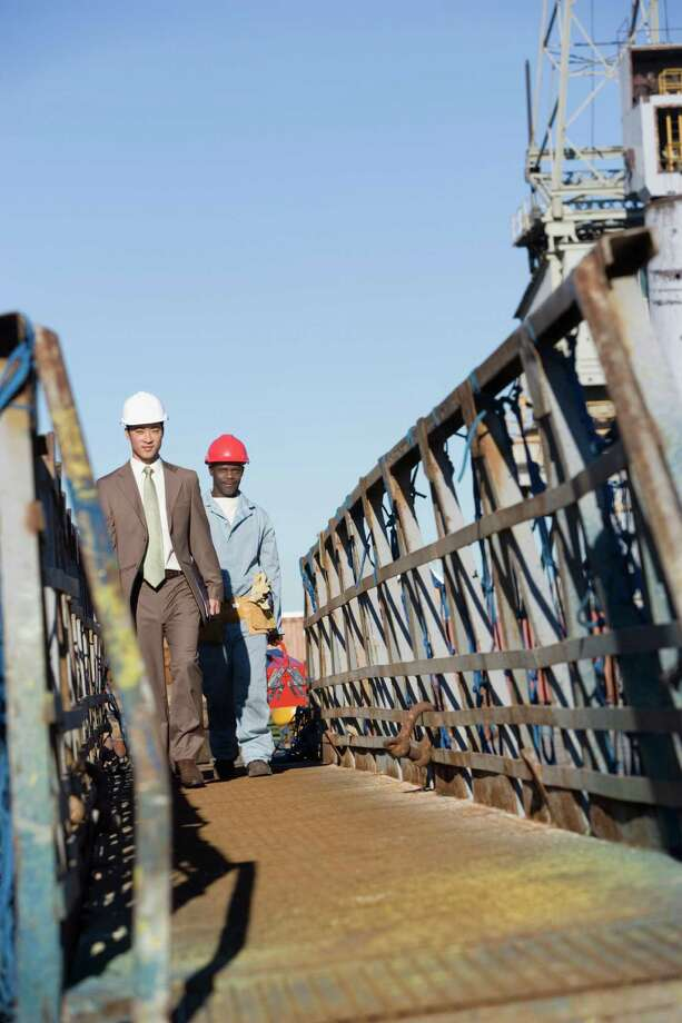 Multi-ethnic businessman and construction worker walking Photo: Klaus Tiedge / Blend Images