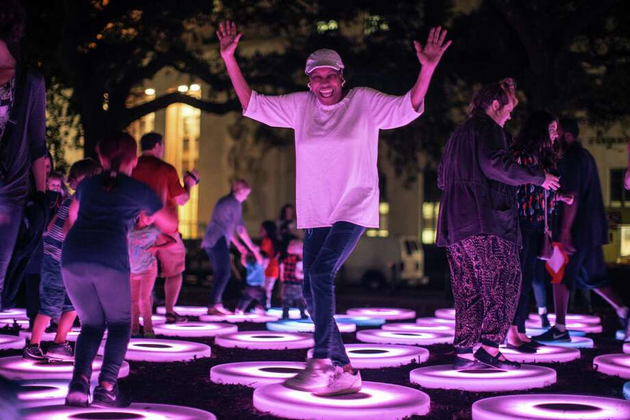This Dec. 3, 2015, photo provided by Arts Council New Orleans shows people interacting with The Pool, a work that was part of New Orleans' LUNA Fete light festival. The work, by artist Jan Lewin, is also going to be on display at Light City Baltimore, a light festival taking place in Baltimore March 28-April 3. Light festivals that combine contemporary art and technology, often with interactive features, are taking off as a trend. Photo: Marcus Alfred Carter /Associated Press / Arts Council New Orleans