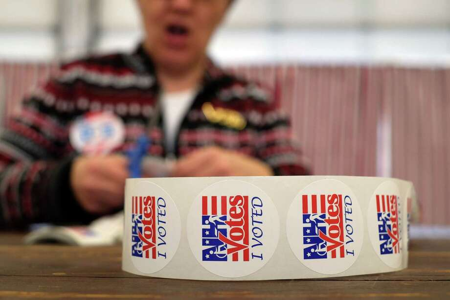 """An electoral official prepares """"I Voted"""" stickers as local residents vote for the first US presidential primary at a fire station in Loudon, New Hampshire, on Feb. 9. This political season's rhetoric and anger might lead one to believe that we are in an era on the order of the End of the Roman Empire. Photo: JEWEL SAMAD /AFP / Getty Images / AFP or licensors"""