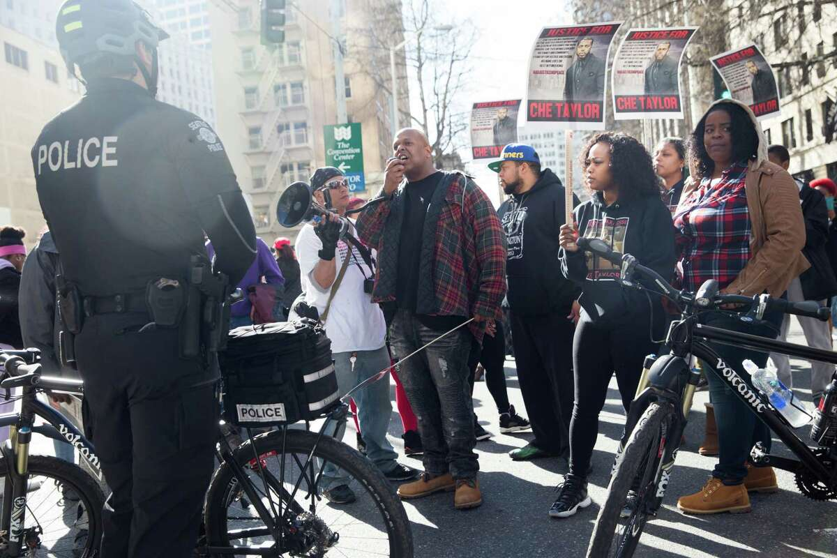 Demonstrators direct their gaze at officers while speaking for change in police behavior towards the black community and blocking the intersection of Seventh Avenue and Stewart Street in protest of the death of Che Taylor, in Seattle on Thursday, Feb. 25, 2016.