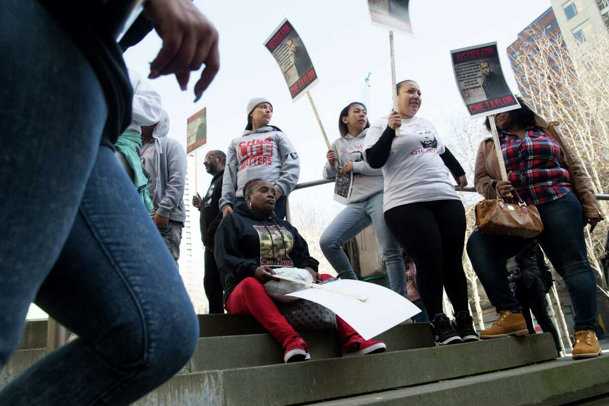 Demonstrators stand on the steps of U.S. District Court in Seattle while protesting the fatal shooting of Che Taylor.