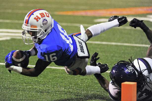 HBU wide receiver D'Angelo Wallace (16) dives past SFA defensive back Keavon Madison for a touchdown during the second half of a college football game, Saturday, October 18, 2014, at Husky Stadium in Houston.