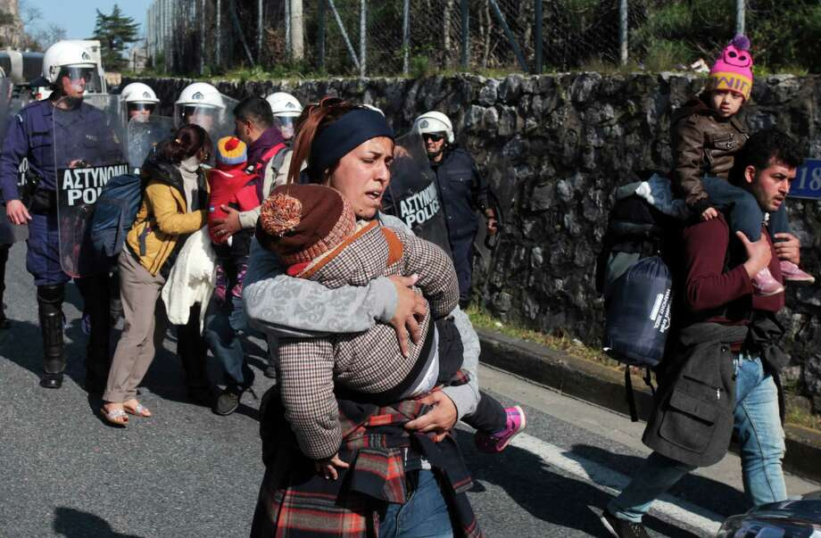 Police scuffle with migrants at a protest Thursday near the city of Larissa in central Greece. Tougher Balkan border controls have left thousands trying to reach Macedonia stranded. Photo: Giorgos Kydonas, STR / InTime News