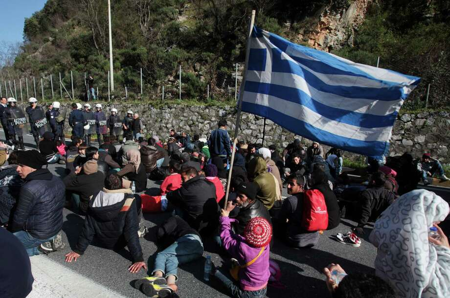 A migrant child holds up a Greek flag as riot police look on, during a protest on a highway at Tempe valley near the city of Larissa, central Greece, on Thursday, Feb. 25, 2016. Tougher Balkan border controls have left thousands of people stranded in Greece, where some 4,000 migrants and refugees continue to arrive daily. Police are stopping buses carrying migrants to the border with Macedonia, leaving hundreds stranded stander along the highway between Athens and the northern city of Thessaloniki. (Giorgos Kydonas/InTime News via AP)  GREECE OUT Photo: Giorgos Kydonas, STR / InTime News