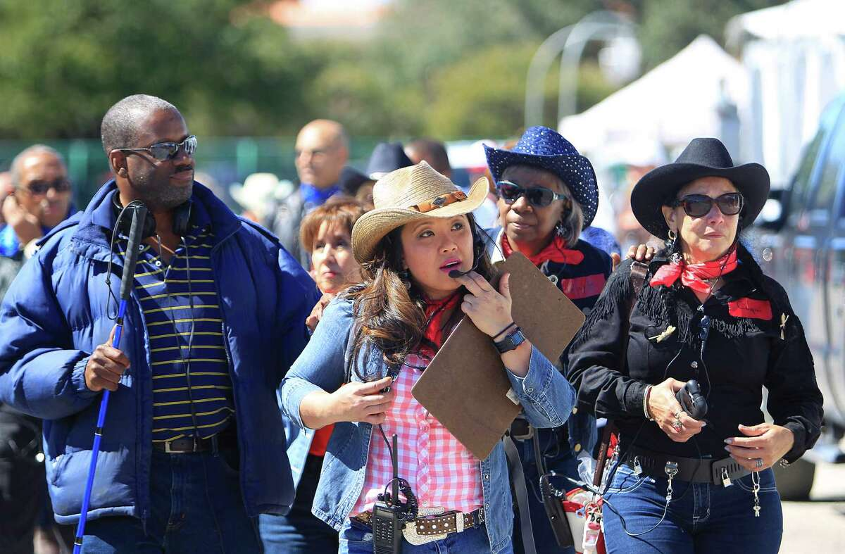 Chelsea Nguyen uses a headset and walkie-talkie to lead a VIP tour of the World's Championship BBQ contest for a group of people who are blind or visually impaired, Thursday, Feb. 25, 2016, in Houston. This is the second year that Nguyen has led the group on a multi-sensory tour of the BBQ contest that comprises everything from talking to pit masters to sampling BBQ.