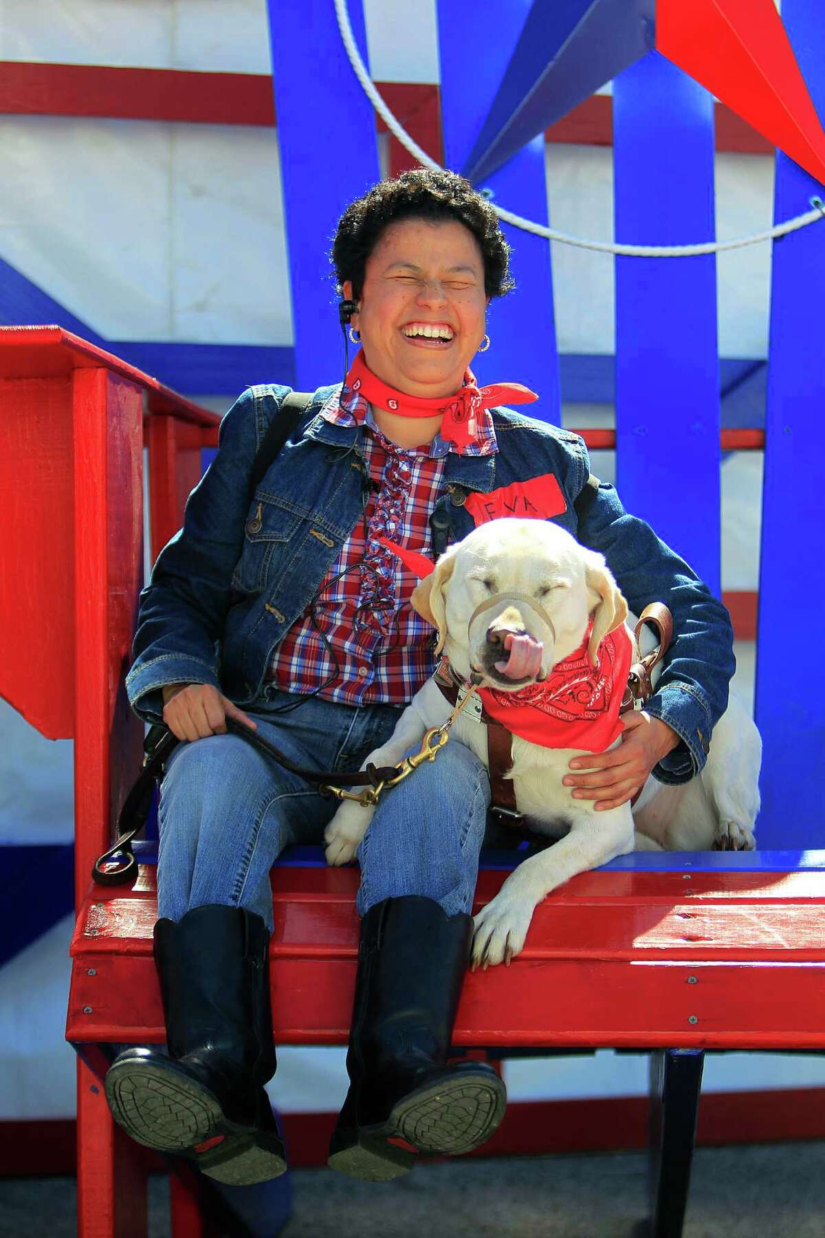 Eva Bergara laughs as she has her picture taken with Kim, her seeing eye dog, in a giant chair during a VIP tour of the World's Championship BBQ contest Thursday, Feb. 25, 2016, in Houston. Vergara, who is blind, was enjoying a multi-sensory tour of the BBQ contest.