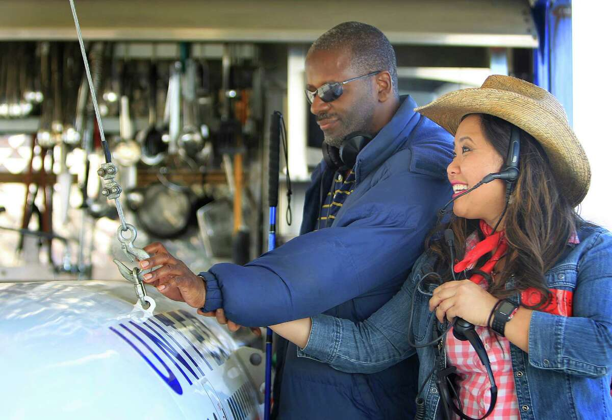 George Battiste and Chelsea Nguyen reach out and feel the apparatus that opens the BBQ pit shaped like a Boeing 777 in United Airlines' area during a VIP tour of the World's Championship BBQ contest Thursday, Feb. 25, 2016, in Houston. This is the second year that volunteer Chelsea Nguyen has lead a group of people who are blind or who have visual impairments on a multi-sensory tour of the BBQ contest.