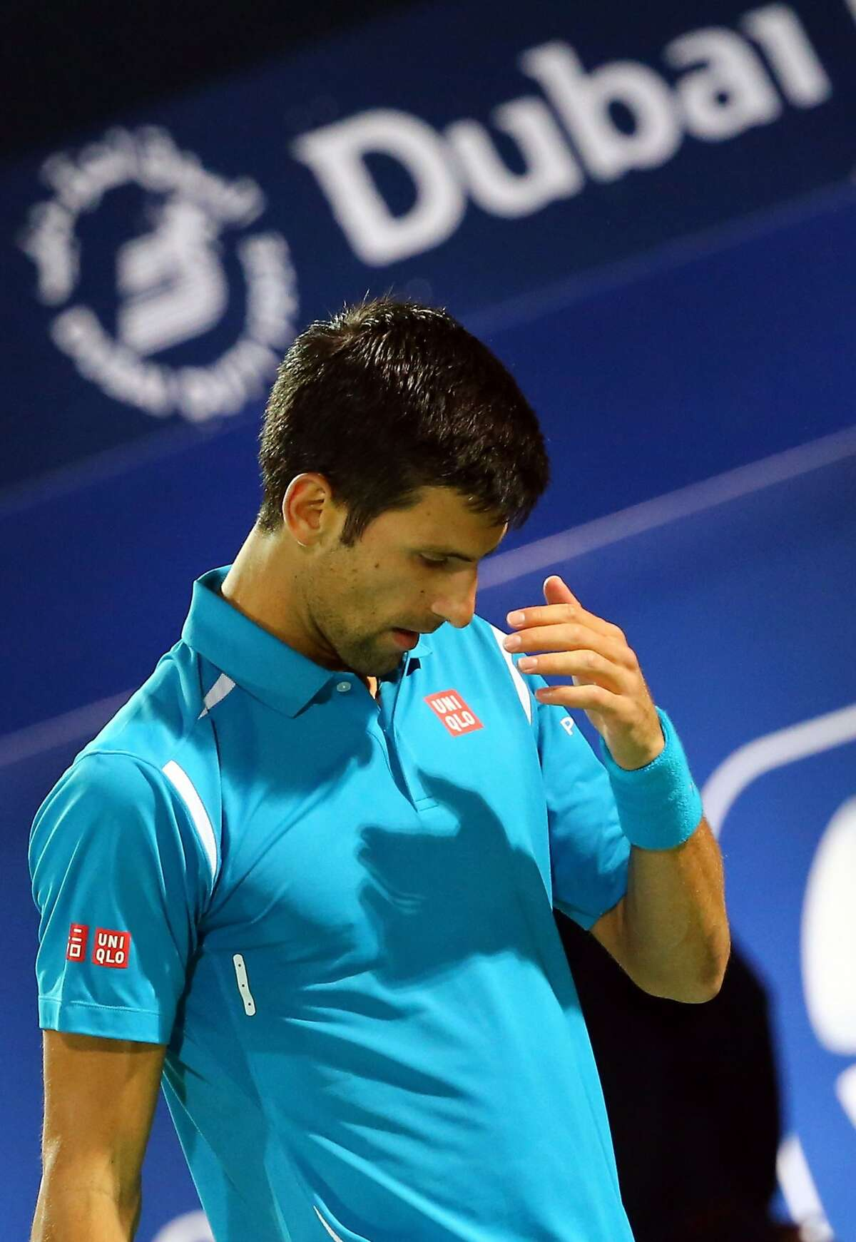 Serbian Novak Djokovic reaches for his right eye during his ATP quarterfinal tennis match against Spain's Feliciano Lopez during the Dubai Duty Free Tennis Championships February 25, 2016. / AFP / MARWAN NAAMANIMARWAN NAAMANI/AFP/Getty Images