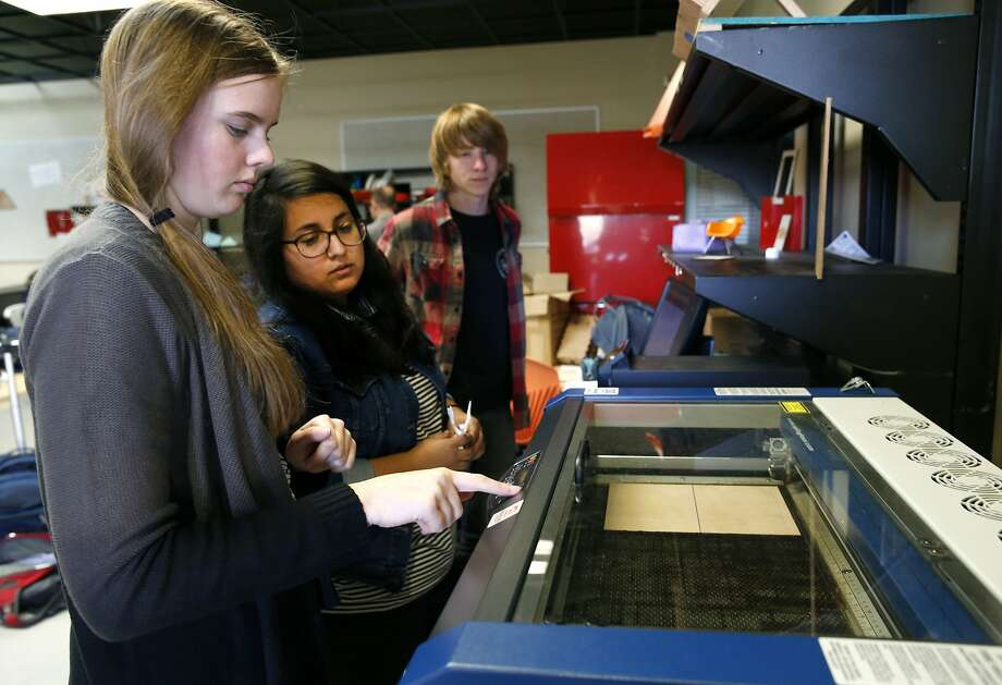 """Cypress Sell (left), a student at the Design Tech High School, programs a laser cutter to make a box """"of a reasonable size"""" with teaching assistant Jasmine Calderon (center) and student Ezra Graves in Burlingame, Calif. on Thursday, Feb. 25, 2016. The charter school has plans to relocate its school to the Oracle campus in the near future. Photo: Paul Chinn, The Chronicle"""