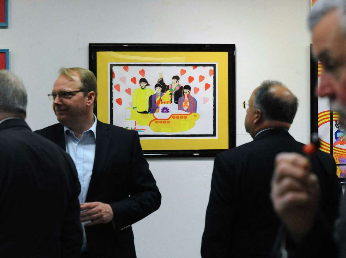 Glenn Feigin (who works in Greenwich), second from right, views a Beatles Yellow Submarine artwork by Ron Campbell an acclaimed cartoonist who worked on major projects like the Beatles Saturday morning cartoon show and Yellow Submarine at the C. Parker Gallery in Greenwich, Conn., Thursday night, Feb. 25, 2016. Campbell will be exhibiting and making appearances to talk cartooning at the C. Parker Gallery through Sunday February 28th.