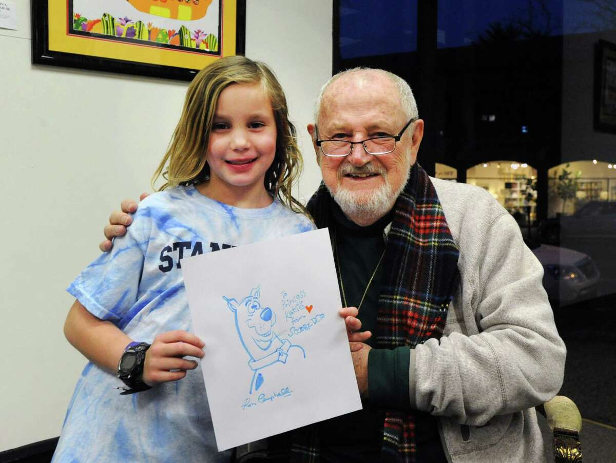 At right, Ron Campbell, an acclaimed cartoonist, with Katie Benincasa, 7, of Greenwich, holding the cartoon dog Scooby-Doo that he drew for her during an appearance to support his show at the C. Parker Gallery in Greenwich, Conn., Thursday night, Feb. 25, 2016. Campbell worked on major projects like Yellow Submarine and the Beatles Saturday morning cartoon show as well as cartoons like Scooby Doo, The Flintstones and Rugrats.