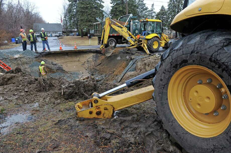 Town of Colonie crews work the site of a water break and sinkhole on Old Niskayuna Road Thursday Feb. 25, 2016 in Latham, N.Y. (Michael P. Farrell/Times Union) Photo: Michael P. Farrell / 10035590A