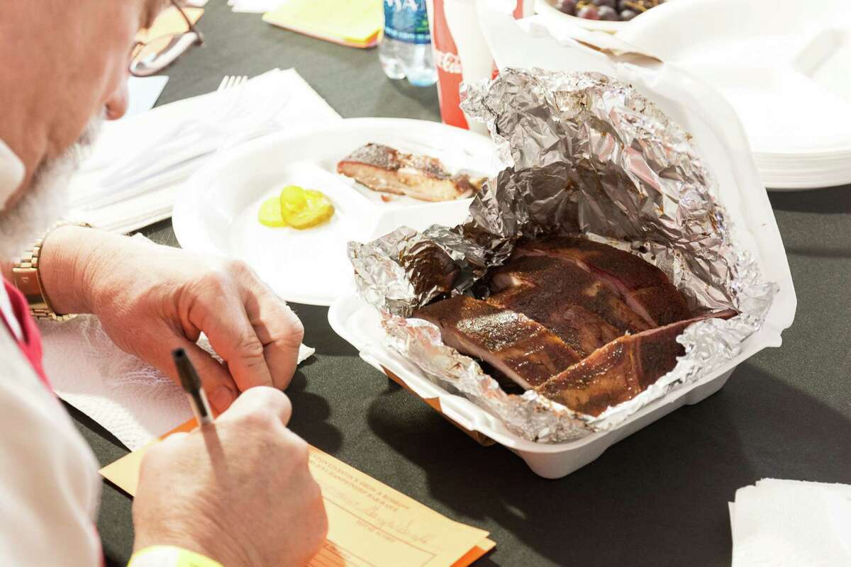 A cook-off judge scores a barbecue sample at the World's Championship Bar-B-Que competition at the Houston Livestock Show and Rodeo in 2015.