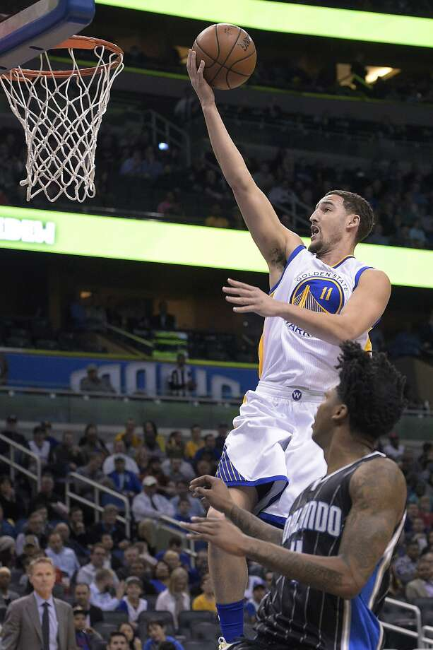 Warriors guard shooting Klay Thompson (11) goes up for a shot in front of Magic point guard Elfrid Payton (4) during Thursday's game in Orlando. Photo: Phelan M. Ebenhack, Associated Press