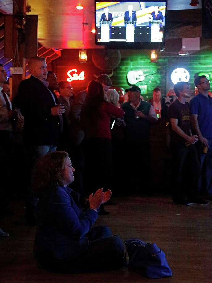 Jennifer Stein sits on the floorat Rebels Honky Tonk, on Washington Avenue,while watching the Republican debate telecast from UH on Thursday. Photo: James Nielsen, Houston Chronicle / © 2016  Houston Chronicle