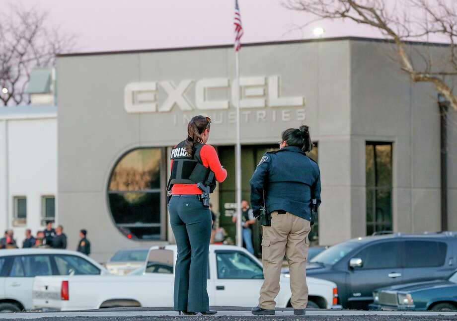 Police guard the front door of Excel Industries in Hesston, Kan., on Thursday after a gunman killed opened fire in the plant parking lot and later in the building. The gunman, believed to be a former employee, was later killed.