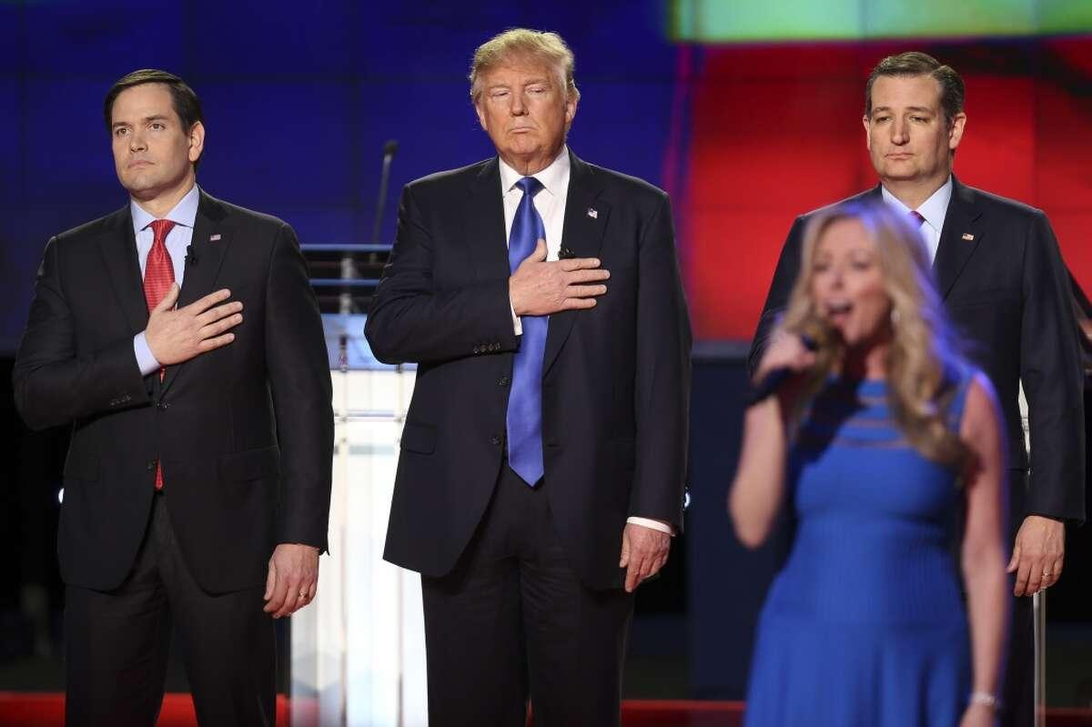 Marco Rubio, Donald Trump y Ted Cruz escuchando el himno nacional estadounidense durante el debate republicano en la Universidad de Houston.