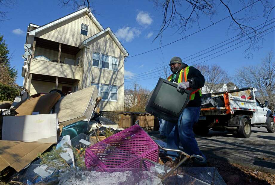 James Taylor, a heavy equipment operator with the City of Stamford Highway Department, cleans up items that were illegally dumped on Givens Avenue. Photo: Matthew Brown / Hearst Connecticut Media / Stamford Advocate