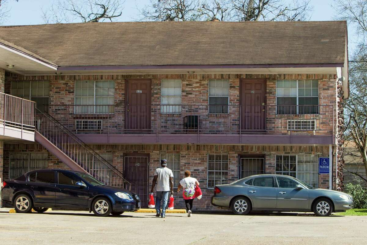 People walk with bags of groceries to an apartment near the intersection of Yellowstone and Sherwood in the Third Ward on Thursday, Feb. 18, 2016, in Houston. Harris County officials are seeking an injuction to prevent nearly 100 suspected gang members from entering the two-square-mile Southlawn community in south Houston. ( Brett Coomer / Houston Chronicle )