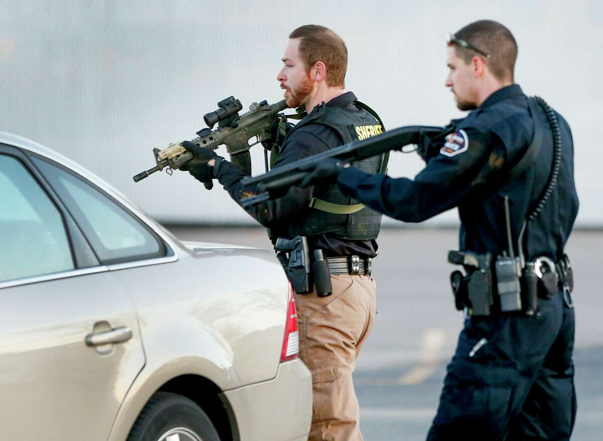 Police look for a possible second shooter in the parking lot of Excel Industries in Hesston, Kan., Thursday, Feb. 25, 2016, where a gunman killed an undetermined number of people and injured many more. (Fernando Salazar/The Wichita Eagle via AP) ORG XMIT: KSWIE102