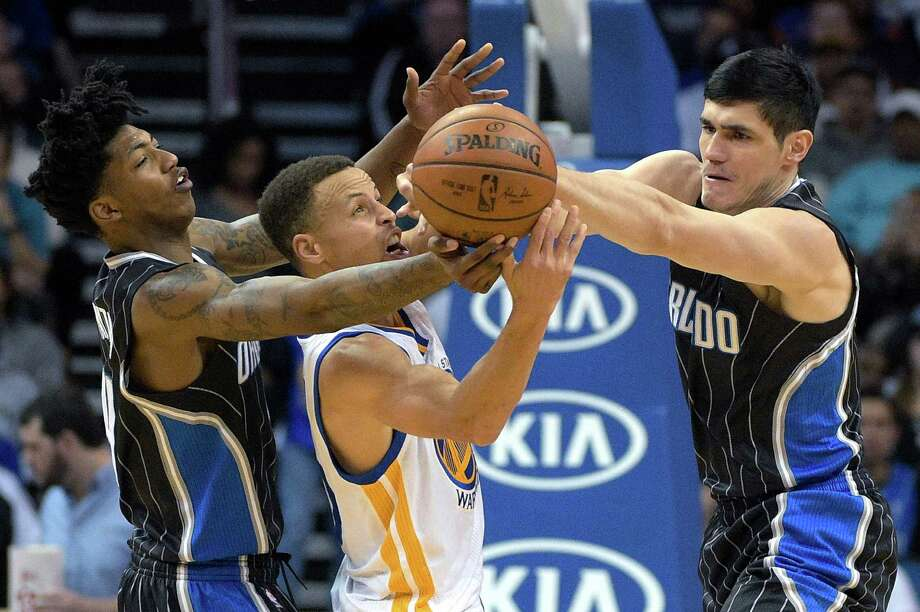 Orlando Magic guard Elfrid Payton (4) and forward Ersan Ilyasova, right, take the ball away from Golden State Warriors guard Stephen Curry, center, during the second half of an NBA basketball game in Orlando, Fla., Thursday, Feb. 25, 2016. The Warriors won 130-114. (AP Photo/Phelan M. Ebenhack) ORG XMIT: DOA114 Photo: Phelan M. Ebenhack / FR121174 AP