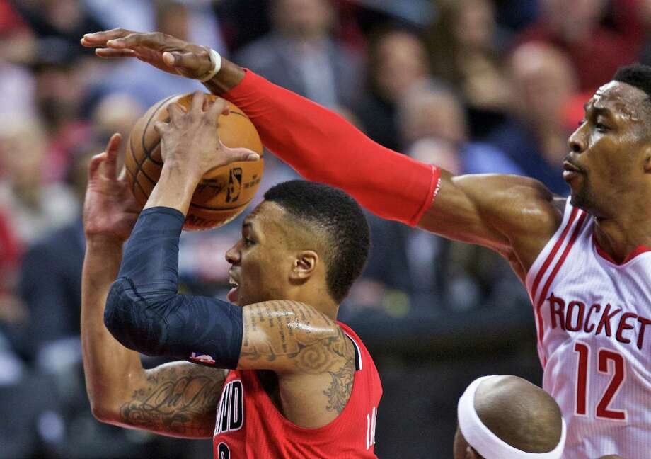 Trail Blazers guard Damian Lillard, left, has his shot blocked by Dwight Howard. Lillard's streak of five consecutive 30-point games ended as he scored 23. Photo: Craig Mitchelldyer, FRE / FR170751 AP