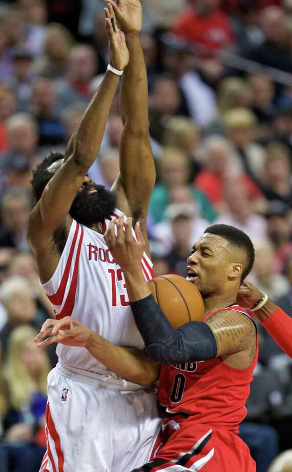 Portland Trail Blazers guard Damian Lillard, right, is fouled by Houston Rockets guard James Harden, left, during the second half of an NBA basketball game in Portland, Ore., Thursday, Feb. 25, 2016. (AP Photo/Craig Mitchelldyer) Photo: Craig Mitchelldyer, Associated Press / FR170751 AP