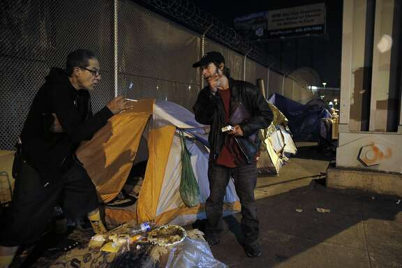 Larry Muraoka, left, gets a cigarette from Patrick Engebretsen outside his tent as homeless residents awaited a 72-hour deadline to leave the area around 13th Street and Division Street in San Francisco , Calif., on Wednesday, February 24, 2016,