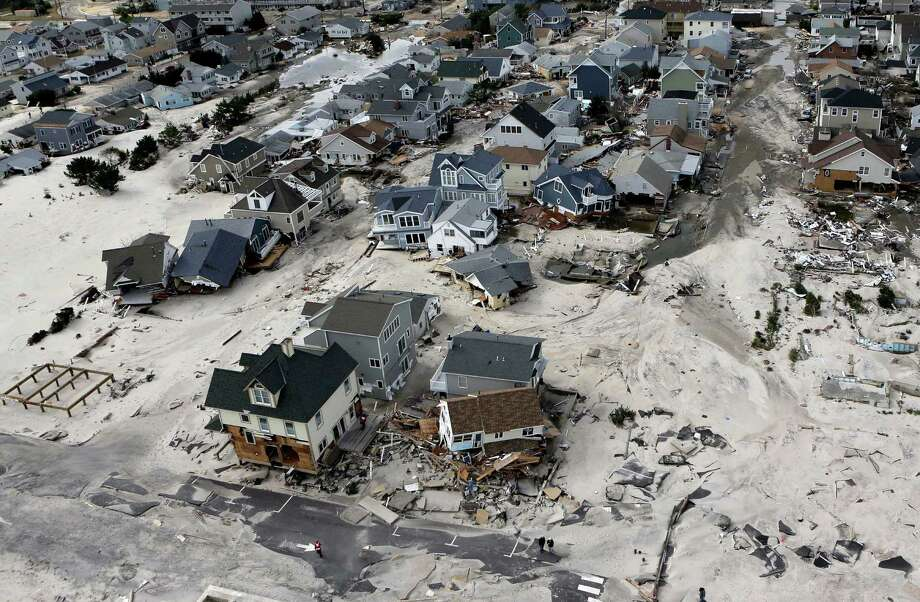 FILE - In this Oct. 31, 2012 file photo, a view from the air shows the destroyed homes left in the wake of Superstorm Sandy in Ortley Beach, N.J.  Sea levels on Earth are rising several times faster than they have in the past 2,800 years and are accelerating because of man-made global warming, according to new studies. An international team of scientists dug into two dozen locations across the globe to see what the sea level was for the past 2,800 years. They charted gently rising and falling seas over centuries and millennia. Until the 1880s and industrialization of society, on average the fastest seas rose was about 1 to 1.5 inches a century, plus or minus a bit. During that time global sea level really didn't get much higher or lower than three inches above or below the 2,000-year average.  (AP Photo/Mike Groll, File) ORG XMIT: WX108 Photo: Mike Groll / AP
