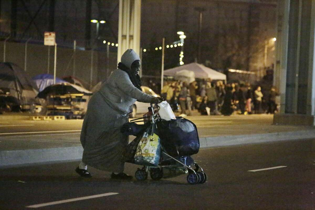 Angela Flax, homeless resident, moves belongings across 13th Street as homelessness supporters stand gathered behind her during a vigil on Friday, February 26, 2016 in San Francisco, California.