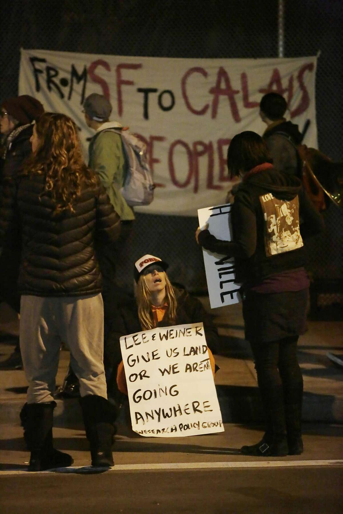 Homeless supporters hold signs along 13th Street during a vigil in the early morning on Friday, February 26, 2016 in San Francisco, California.