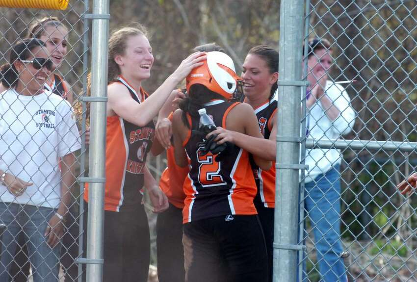 Stamford's Brittany Ulloa is celebrates with teammates Clare Kapinski, left, and Chelsea Sciarretta after scoring during OT as Trinity Catholic hosts Stamford High in a girls softball game Wednesday afternoon, April 7, 2010.