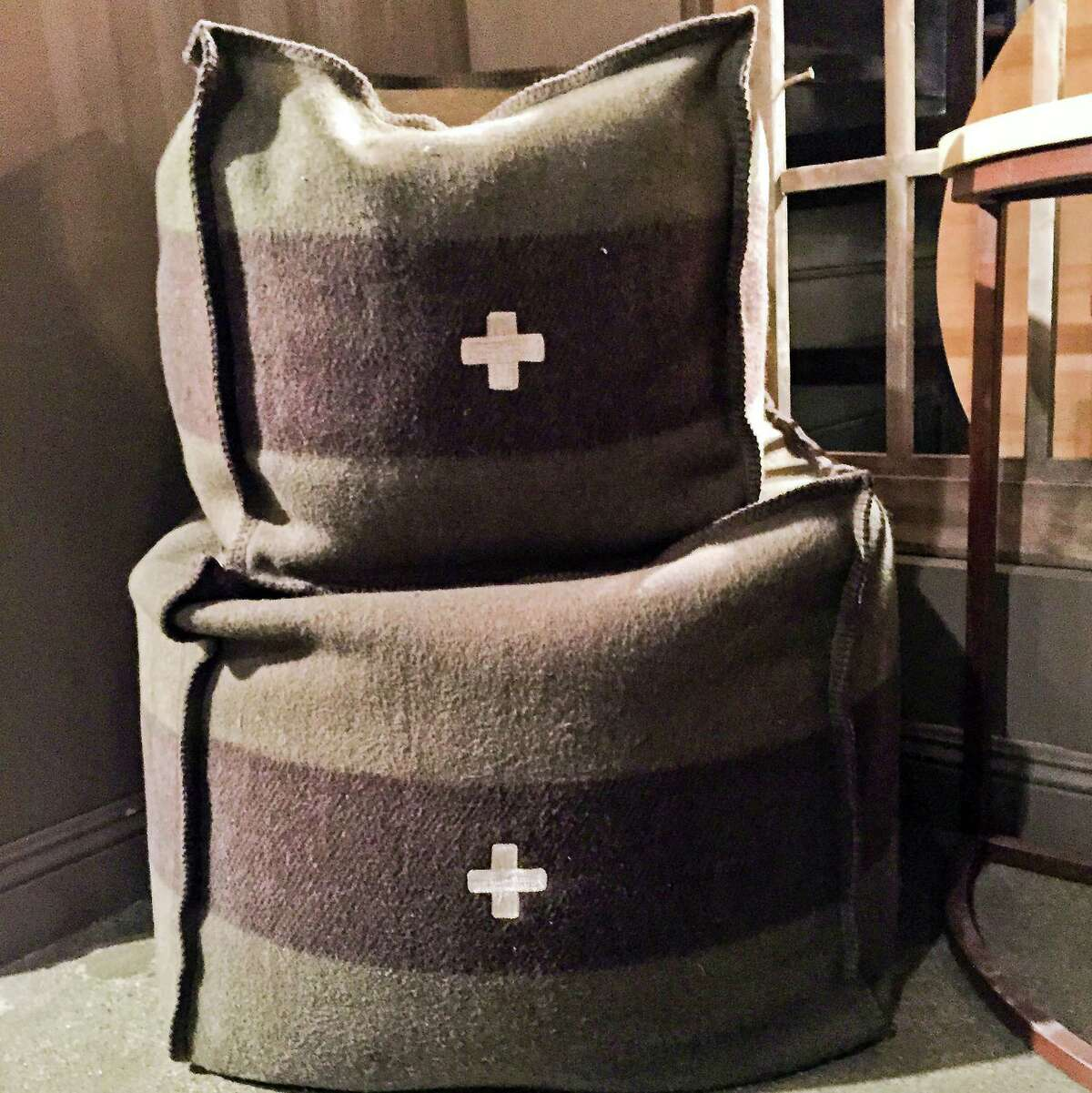 Swiss Army green and brown poufs by BoBo Intriguing Objects. They also come in black and cream, brown and red and gray and black. (Patricia Sheridan/Pittsburgh Post-Gazette/TNS)
