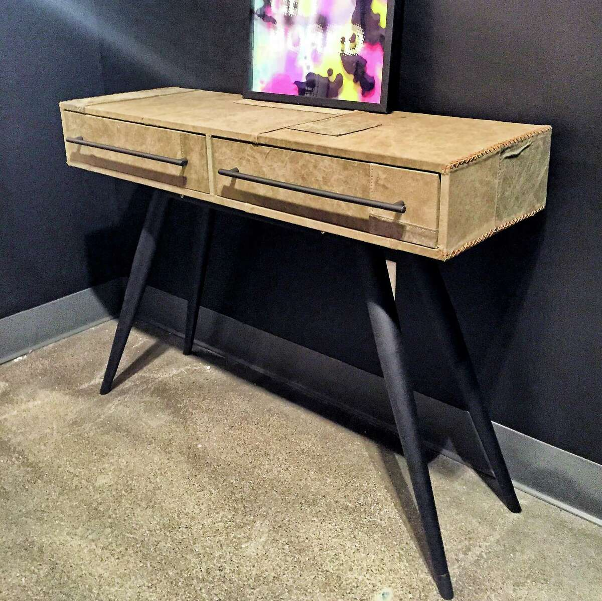 The Trunk Console table by United Strangers is made with patched vintage army tent fabric on a distressed black metal base with cross stitch accents. (Patricia Sheridan/Pittsburgh Post-Gazette/TNS)