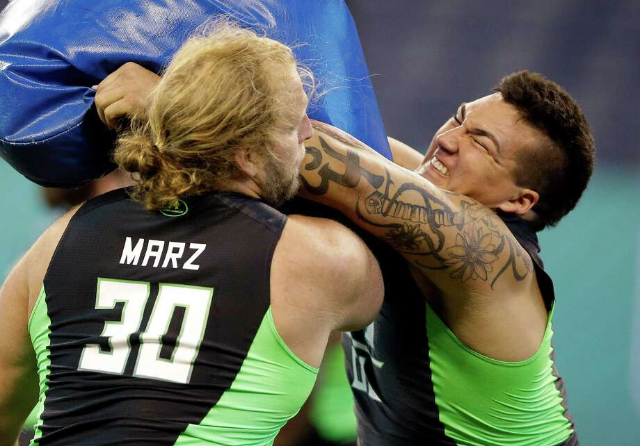 Wisconsin offensive lineman Tyler Marz, left, and UCLA offensive lineman Alex Redmond run a drill at the NFL football scouting combine on Friday, Feb. 26, 2016, in Indianapolis. (AP Photo/Darron Cummings) Photo: Darron Cummings, Associated Press / AP