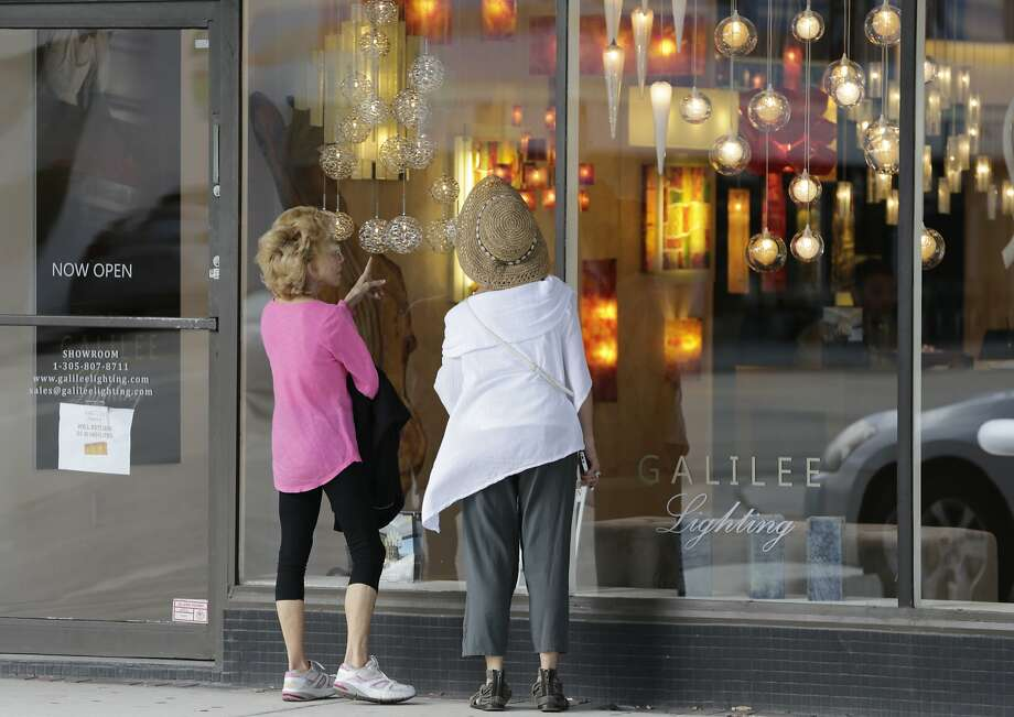 Shoppers check the window of a lighting store in Miami Beach this week. Consumer spending grew in January. Photo: Lynne Sladky, Associated Press